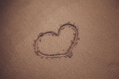 Símbolo del corazón del vintage en la playa arenosa Imágenes de archivo libres de regalías