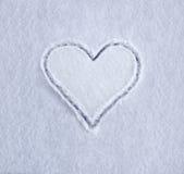 Símbolo del corazón drenado en nieve Imagenes de archivo