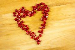 Símbolo del corazón hecho de los gérmenes de la granada Imagenes de archivo