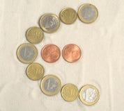 Símbolo del euro con las monedas euro Foto de archivo libre de regalías
