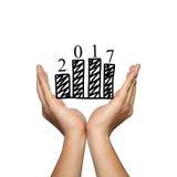 Símbolo del gráfico de barra del negocio y del número 2017 en la entrega del hombre Foto de archivo libre de regalías