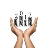 Símbolo del gráfico de barra del negocio y del número 2017 en la mano del hombre en concentrado imagen de archivo