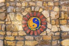 Símbolo del mosaico de Yin y de yang en la pared de piedra imagenes de archivo