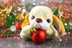 Símbolo del perro de juguete del Año Nuevo 2018 rodeado por los elementos de la Navidad y las ramas decorativos del abeto Imagen de archivo