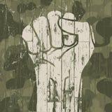 Símbolo del puño (revolución) en fondo del camuflaje de los militares Foto de archivo libre de regalías