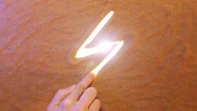 Símbolo del relámpago del dibujo de la mano en la arena Seashell de la concha de peregrino en color de rosa Visión superior almacen de metraje de vídeo