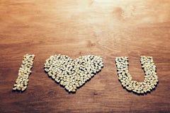 Símbolo del ` del ` te amo hecho fuera de pequeños corazones de madera Fotografía de archivo