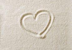 Símbolo do coração tirado na foto do macro da superfície da areia fotos de stock royalty free