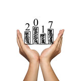 Símbolo do gráfico de barra do negócio e do número 2017 na mão do homem em concentrado Imagem de Stock