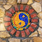 Símbolo do mosaico de Yin e de yang na parede de pedra imagens de stock royalty free
