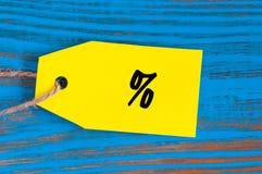 Símbolo dos por cento do pano na etiqueta amarela no fundo de madeira azul Projete para a venda, disconto, propaganda, preço de m Fotos de Stock