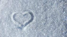 Símbolo en la nieve, porción del corazón de copos de nieve que vuelan en el viento almacen de video