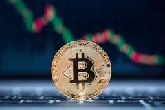 Símbolo físico de la moneda de Bitcoin en el ordenador portátil con el fondo del gráfico del precio de la tendencia bajista, mone Foto de archivo