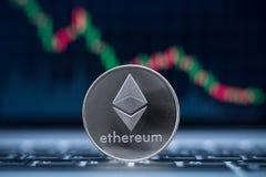 Símbolo físico de la moneda de Ethereum en el ordenador portátil con el fondo del gráfico del precio de la tendencia bajista Imagen de archivo
