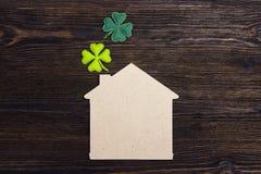 Símbolo home afortunado com trevo de quatro folhas no fundo de madeira Co foto de stock royalty free