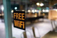 Símbolo libre de Wi-Fi en la ventana en un café con 1 hermoso bokeh de 4 aberturas imagenes de archivo