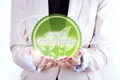 símbolo natural de 100% nas mãos da mulher Fotos de Stock Royalty Free