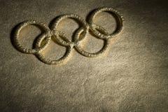 Símbolo olímpico dos anéis do ouro sob o projetor Fotografia de Stock Royalty Free