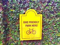 Símbolo que parquea de la bicicleta en fondo verde de la hoja imagenes de archivo