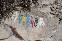 Símbolo religioso nepalês que escreve em uma rocha fotografia de stock royalty free
