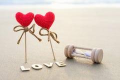 Símbolo romántico de dos corazones rojos en la superficie de la arena Fotografía de archivo libre de regalías