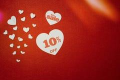 Símbolo romántico en venta bajo la forma de corazón con el diez por ciento al lado de otros corazones blancos más pequeños en el  foto de archivo