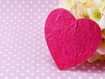 Símbolo rosado del corazón con la hortensia de flores artificiales Foto de archivo