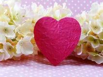 Símbolo rosado del corazón con la hortensia de flores artificiales Imagen de archivo libre de regalías