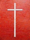 Símbolo transversal da alvenaria contra uma parede de tijolo vermelho Foto de Stock