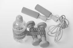 Símbolos da saúde e da aptidão Corda de salto, água e barbells foto de stock royalty free