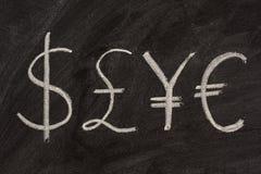 Símbolos de cuatro dinero en circulación en la pizarra Foto de archivo libre de regalías