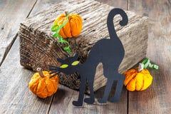 Símbolos de Dia das Bruxas: um gato preto e uma abóbora feitos do papel Fotografia de Stock Royalty Free