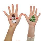 Símbolos de la Navidad pintados en las manos Árbol de navidad y hombre de la nieve Fotos de archivo libres de regalías