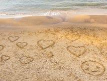 Símbolos de los corazones y del dibujo redondo de la cara en la arena en la playa del teléfono Baruch 'promenade' de Tel Aviv Isr imagenes de archivo