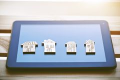 Símbolos de madeira das casas no tablet pc digital Fotos de Stock