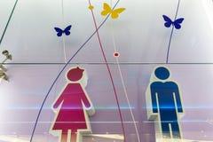 Símbolos divertidos del lavabo del wc - muestra del retrete en aeropuerto público imagenes de archivo