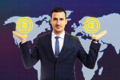 Símbolos do euro e do dólar da terra arrendada do homem nas palmas fotos de stock