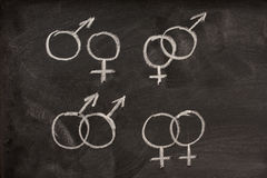 Símbolos masculinos y femeninos del género en la pizarra Fotografía de archivo libre de regalías
