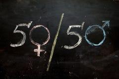 Símbolos o muestras del género para el varón y el sexo femenino dibujados en una pizarra imagen de archivo libre de regalías