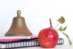 Símbolos para a educação, vermelho - maçã caseiro deliciosa, sino de escola de bronze empilhado na espiral preta - caderno encade fotos de stock royalty free