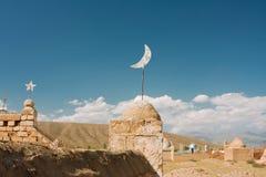 Símbolos religiosos nos túmulos e nas lápides velhos de cemitérios muçulmanos em Ásia Fotografia de Stock Royalty Free