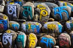 Símbolos religiosos tibetanos do budhist em pedras Fotos de Stock Royalty Free