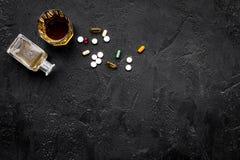 Síndrome Hungover alcoholism Vidro e comprimidos no espaço preto da cópia da opinião superior do fundo fotografia de stock