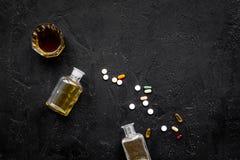 Síndrome Hungover alcoholismo Vidrio y píldoras en espacio negro de la copia de la opinión superior del fondo Imagen de archivo