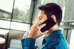 Sócio de consulta do homem de negócios pelo telefone ao sentar-se na cafetaria imagem de stock