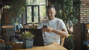 Sócio de espera do homem de negócios novo caucasiano no jogo moderno do café e do jogo no smartphone Vestir de sorriso profission video estoque