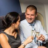 Sócios comerciais da cabine do voo que brindam o champanhe foto de stock