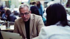 Sócios comerciais do homem e da mulher com o portátil que senta-se em um café na cidade, falando filme