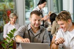 Sócios comerciais dos homens que trabalham no café do portátil fotografia de stock royalty free