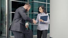 Sócios comerciais homem e reunião da mulher perto da entrada ao prédio de escritórios filme